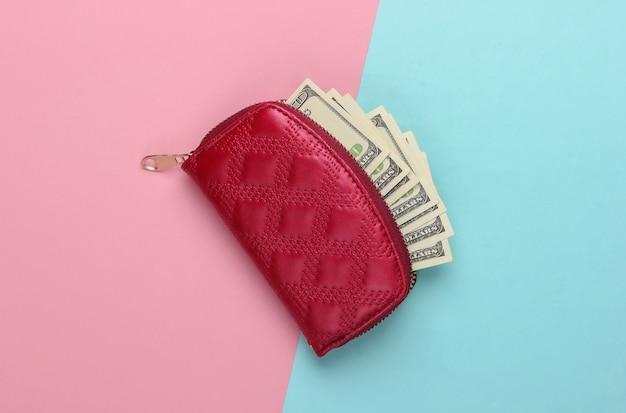 Rote brieftasche mit hundert dollarnoten auf einem blau-rosa pastell.