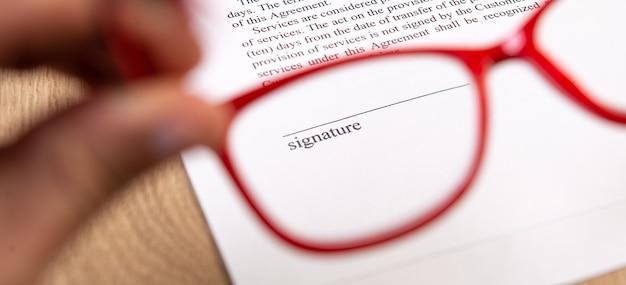 Rote brille in der hand und platz zur unterzeichnung des vertrages.