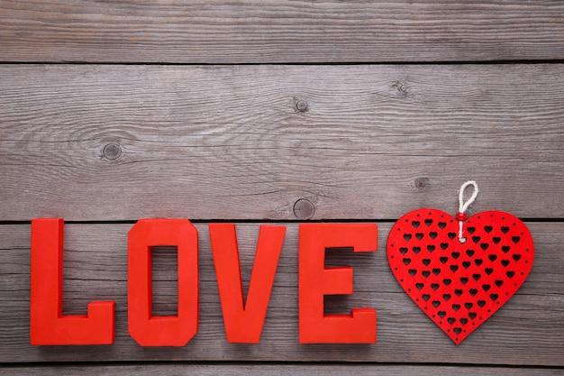 Rote buchstaben lieben und herz auf grauem hintergrund. liebe wort.