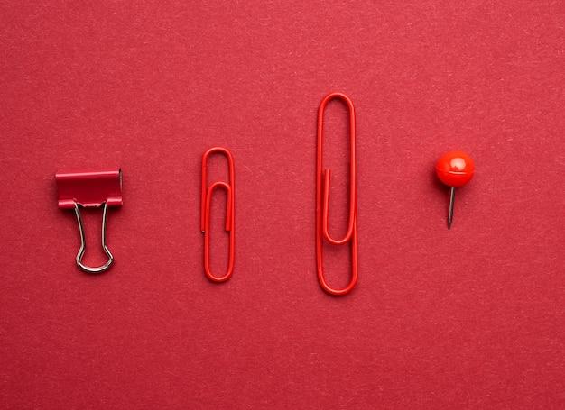Rote büroklammern aus metall, knopf auf einem roten feld