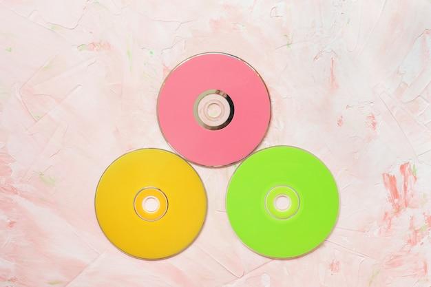 Rote cd- oder dvd-discs auf rosa minimalistischem retro-hintergrund