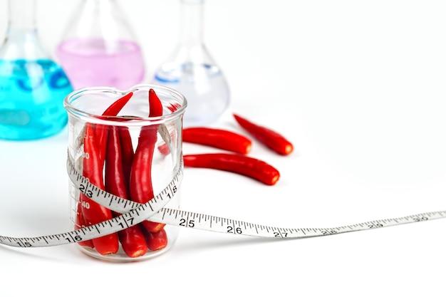 Rote chili im becherglas mit maßband mit medizin