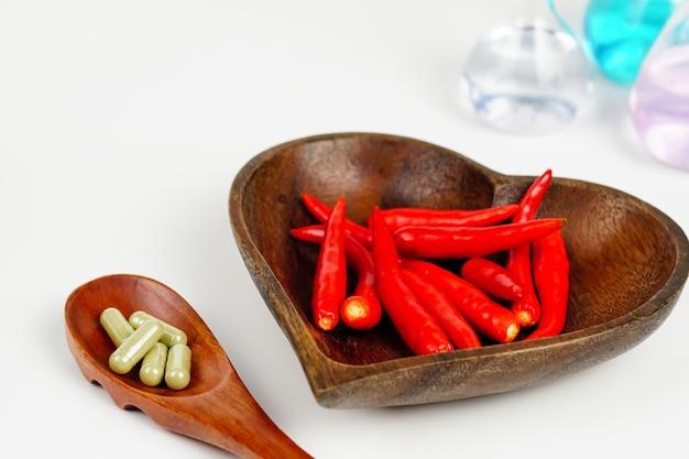 Rote chili in einer herzförmigen holzschale und medizin auf einem holzlöffel
