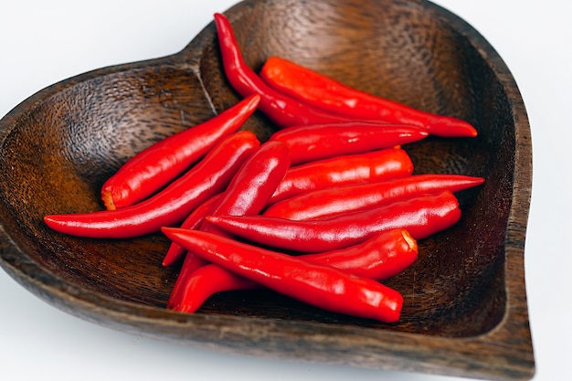 Rote chili in herzförmiger holzschale