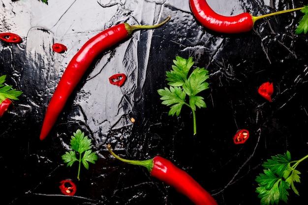 Rote chilischote und petersilie auf schwarzer oberfläche, würzige oberfläche,