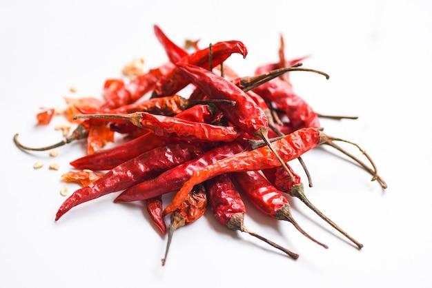 Rote chilischote und samen, getrocknete rote chilischote oder chili-cayennepfeffer isoliert auf weißem hintergrund