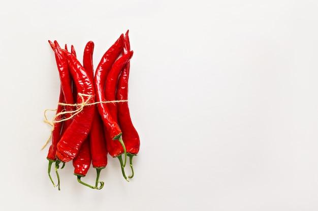 Rote chilischoten auf hellgrauem holztisch