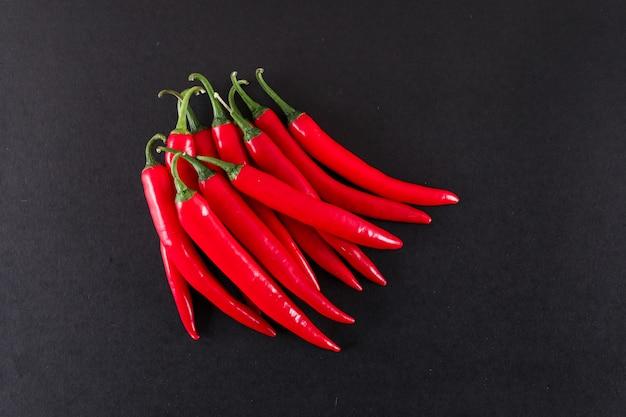 Rote chilischoten auf schwarzer oberfläche
