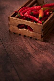 Rote chilischoten in einer schachtel auf einer holzoberfläche