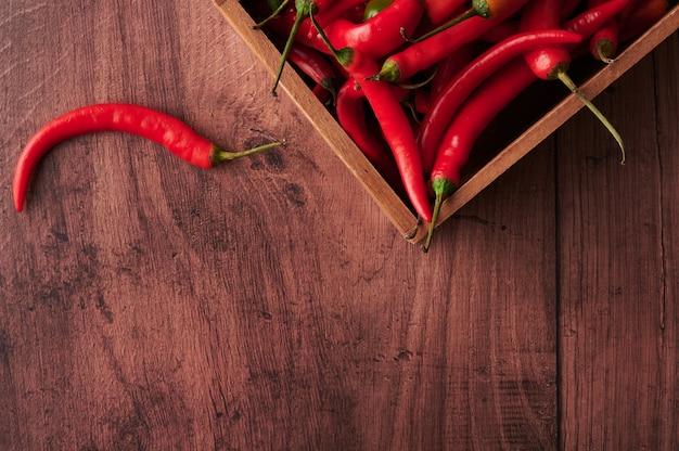Rote chilischoten in einer schachtel auf holzoberfläche
