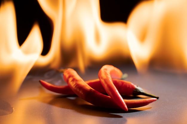 Rote chilischoten. scharfer roter silikulosepfeffer gegen eine flamme.