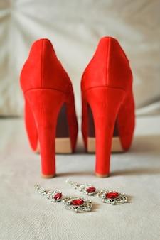 Rote damenschuhe stehen auf der fensterbank, hochzeit, boutonniere.