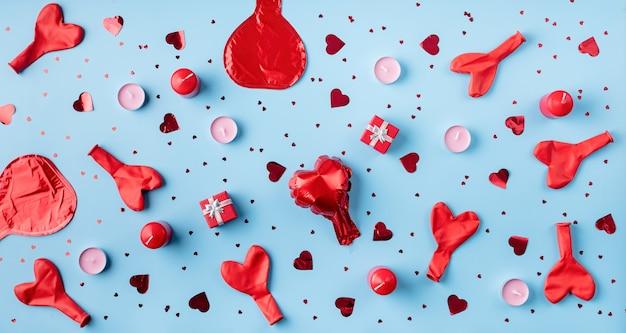 Rote dekorationen luftballons, kerzen, konfetti und geschenke draufsicht flach auf blau liegen