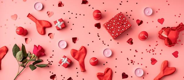 Rote dekorationsballons, kerzen, konfetti und geschenke draufsicht flach lagen auf rosa hintergrund
