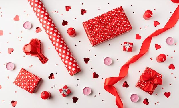 Rote dekorationsballons, kerzen, konfetti und geschenke draufsicht flach lagen auf weißem hintergrund