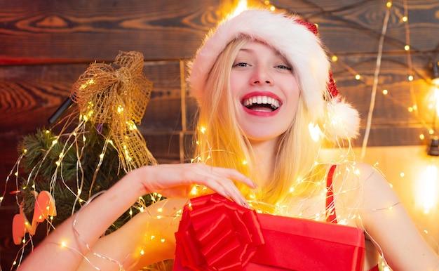 Rote dessous für weihnachten. mädchen santa hut zu hause in der nähe von weihnachtsbaum. sexy erotisches mädchen.