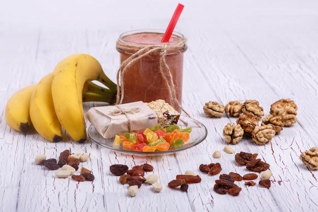 Rote detox coctail mit bananen, walnuss und kandierte früchte liegt auf weißem tisch