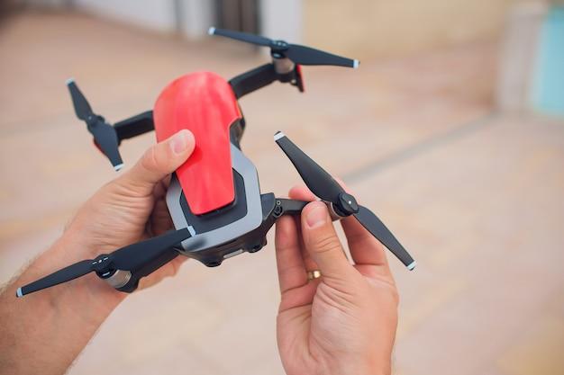 Rote drohne, die kontrolle durch mannhände fängt. legt propeller aus