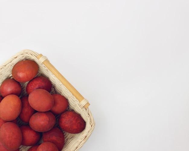 Rote eier im korb auf weiß