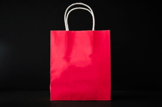 Rote einkaufstasche auf schwarzer tabelle