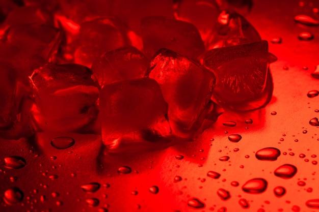 Rote eiswürfel auf einem reflektierenden tisch mit wassertropfen nahaufnahme