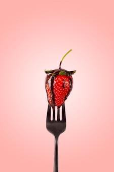 Rote erdbeere auf einer gabel mit schmelzschokolade.