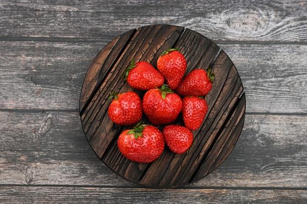 Rote erdbeere liegt auf einem dunklen hölzernen hintergrund, draufsicht
