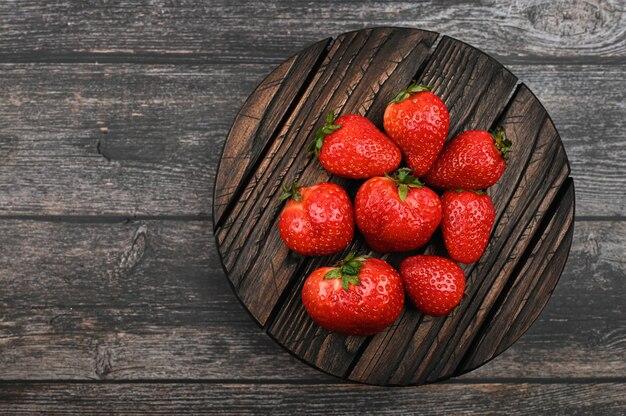 Rote erdbeere liegt auf einem runden holzbrett