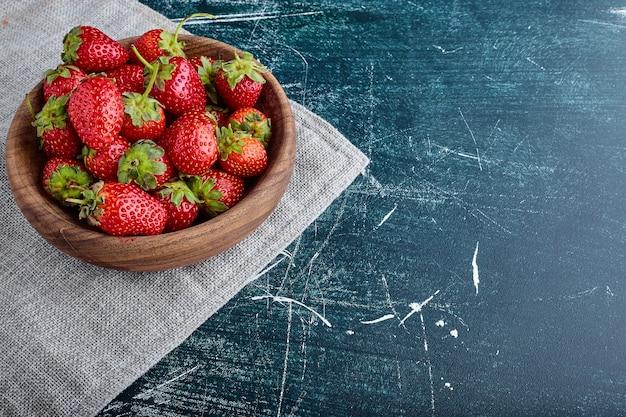 Rote erdbeere lokalisiert auf blauem hintergrund in einer hölzernen tasse.