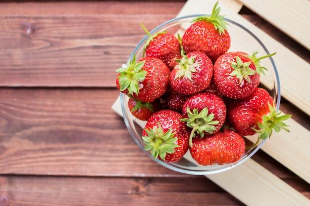 Rote erdbeere lokalisiert auf holztisch