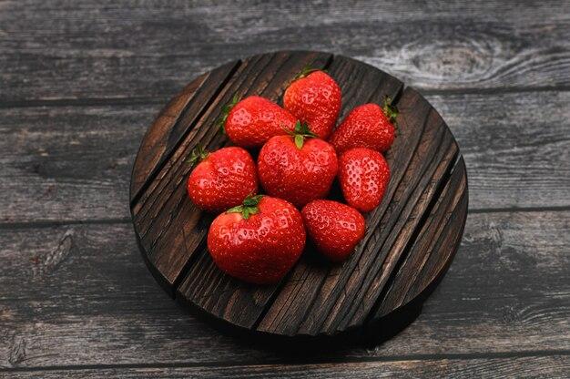 Rote erdbeeren auf dunklem hölzernem hintergrund