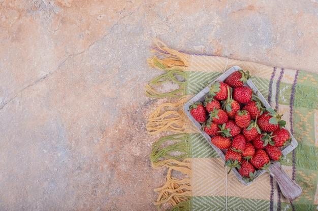 Rote erdbeeren auf quadratischer rustikaler platte.