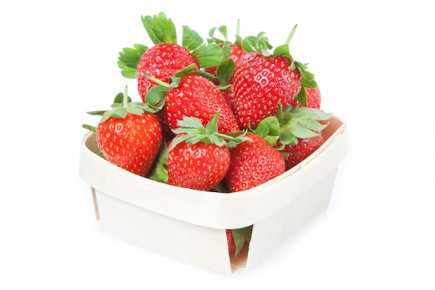 Rote erdbeeren in einem korb. nahansicht. an einer weißen wand.