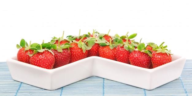 Rote erdbeeren in einer porzellanschale. nahansicht. an einer weißen wand.