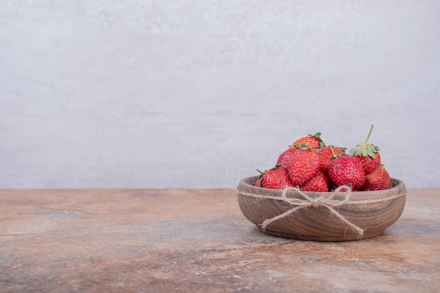 Rote erdbeeren in einer rustikalen holzschale.