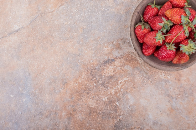 Rote erdbeeren in einer rustikalen holzschale
