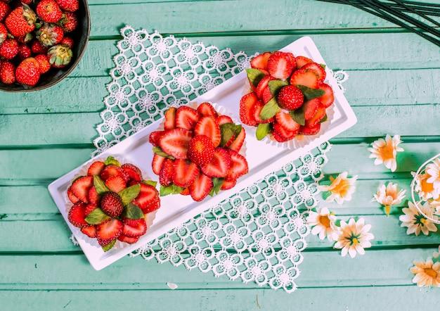 Rote erdbeertartalettes der blumenform auf dem tisch.