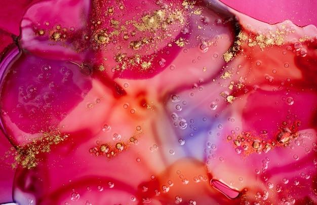 Rote farbe befleckt hintergrund mit flüssiger transparenter beschaffenheit des goldglitters mit blasen