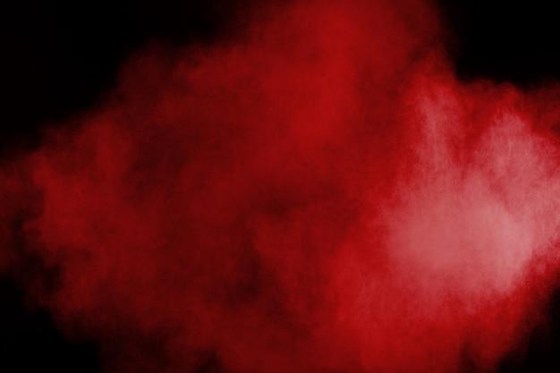 Rote farbpulverexplosion auf schwarzem