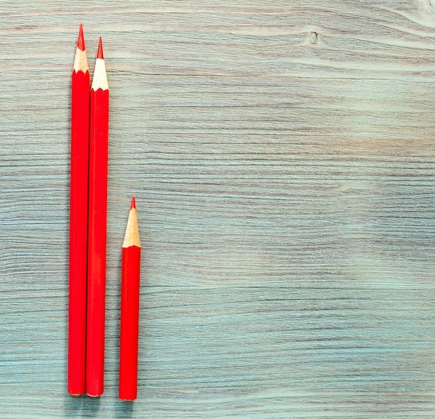 Rote farbstifte zwei lange, eine kurze auf türkisblauer natürlicher holztischplatte. nahansicht. draufsicht. selektiver weichzeichner. . textkopierplatz.