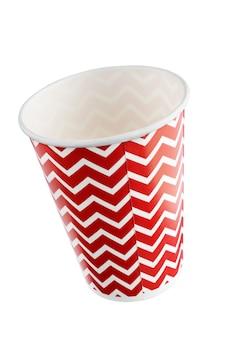 Rote festliche pappbecher mit einem muster aus unterbrochenen horizontalen linien. + beschneidungspfad