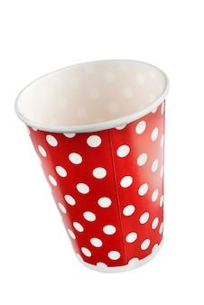 Rote festliche pappbecher mit einem muster aus weißen erbsen. + beschneidungspfad