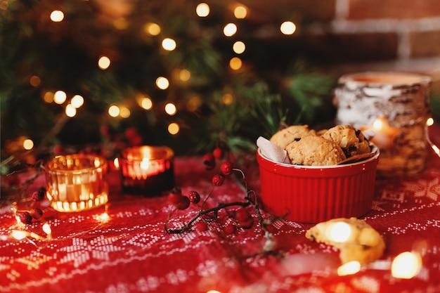 Rote festliche schüssel voll mit weihnachtsplätzchen verwischte weihnachtstannenbaumlichter