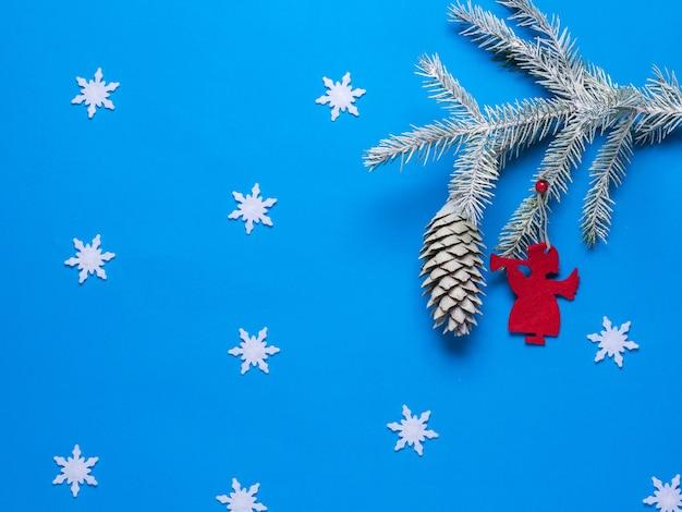 Rote figur eines engels in einem fichtenzweig mit schneeflocken. vorbereitung auf weihnachten