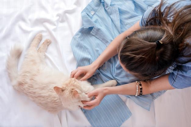 Rote flauschige katze, die auf bett mit pyjamas liegt. schöne junge frau mit niedlichem kätzchen