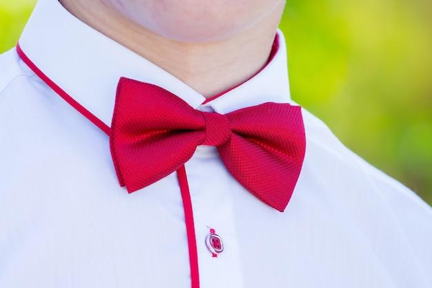 Rote fliege auf einem weißen hemd eines jungen mannes