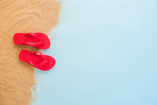 Rote flipflops auf sand