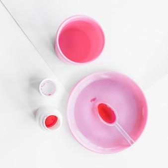 Rote flüssige medizin im löffel auf der rosa platte mit flasche und glas auf weißbuch