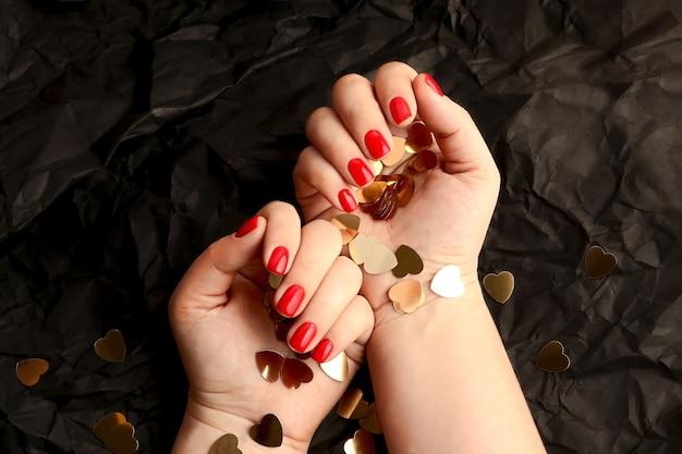 Rote frauenmaniküre auf dem kunstschwarzhintergrund. verführerische farbe. glänzende nageloberfläche. goldenes herzförmiges konfetti in den händen. glückliches valentinstagkonzept.