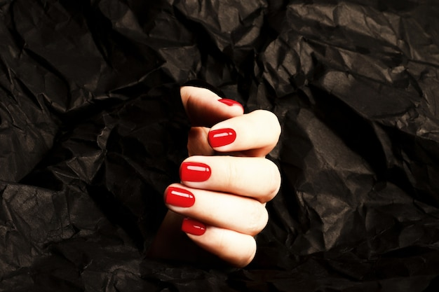 Rote frauenmaniküre auf dem kunstschwarzhintergrund. verführerische farbe. glatte nageloberfläche.